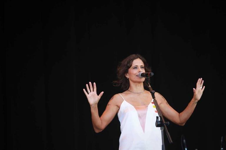 A cantora Zélia Duncan está de pé em um palco, cantando em frente ao microfone, com os braços abertos