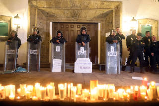 Riot police guard the entrance of the governor's official residence during a vigil in memory of three film students that were kidnapped and killed by gunmen after being confused with members of a rival gang, in Guadalajara