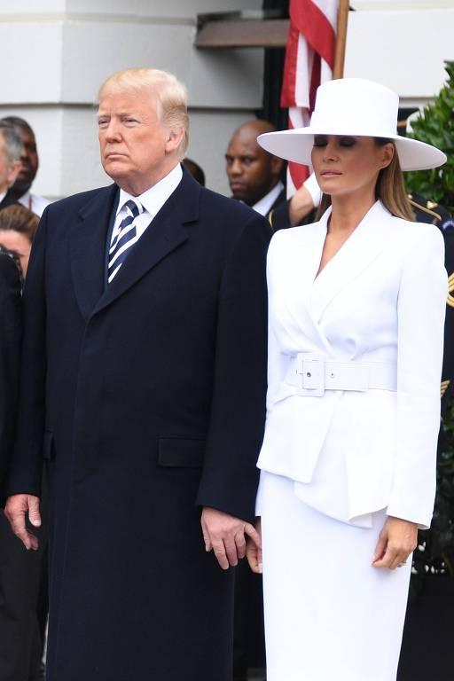 Presidente dos EUA Donald Trump tentando segurar a mão de sua esposa, Melania Trump