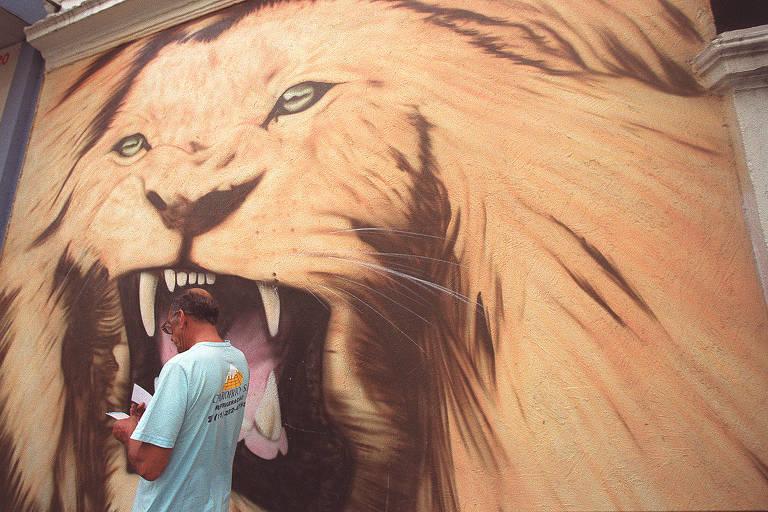 Homem passa em frente a pintura de leão em parede na região central de São Paulo