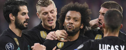 Madrid's Marcelo, center,  is congratulated by his teammates after scoring his side's first goal during the soccer Champions League first leg semifinal soccer match between FC Bayern Munich and Real Madrid in Munich, southern Germany, Wednesday, April 25, 2018. (Sven Hoppe/dpa via AP) ORG XMIT: FOS116
