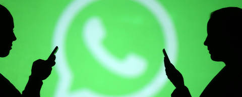 Silhouettes of mobile users are seen next to a screen projection of Whatsapp logo in this picture illustration taken March 28, 2018.  REUTERS/Dado Ruvic ORG XMIT: DAD125