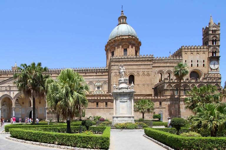 Fachada da catedral de Palermo, que tem tom ocre dos tijolos usados na construção. À sua frente, há uma praça com um jardins com árvores e arbustos e estátuas