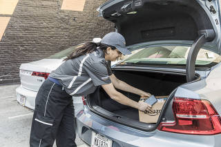 A worker demonstrates the delivery of an Amazon package to a vehicle's trunk in San Francisco.
