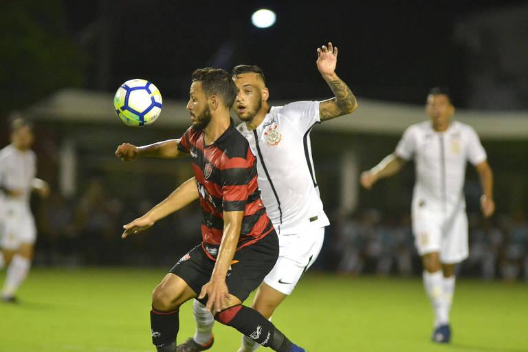 Jogadores de Corinthians e Vitória disputam a bola no Barradão