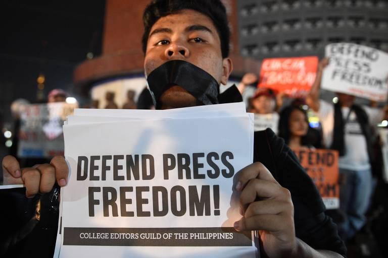 """Homem aparece com fita adesiva preta tapando a boca e carrega um cartaz, com a expressão, em inglês, """"Defenda a liberdade de imprensa""""; ao fundo, outras pessoas aparecem com cartazes"""