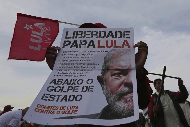 """Homem, que não aparece na imagem, carrega cartaz com as mensagens """"Liberdade para Lula"""" e """"Abaixo o golpe de Estado""""; ao fundo à esquerda, aparece uma bandeira vermelha com a expressão """"Lula Livre"""" e a estrela do PT"""