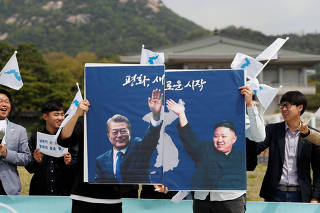 Students hold posters with pictures of South Korea's President Moon Jae-in and North Korea's leader Kim Jong Un during a pro-unification rally ahead of the upcoming summit between North and South Korea in Seoul