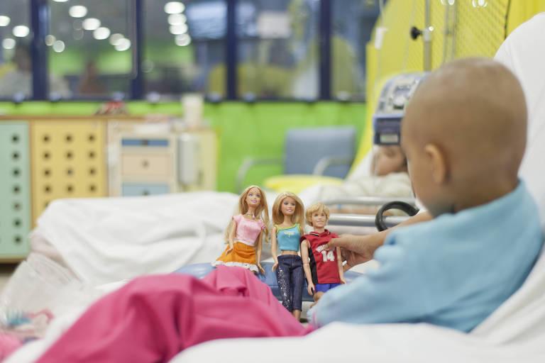 Criança com câncer, na cama, em hospital oncológico, segura bonecas e boneco