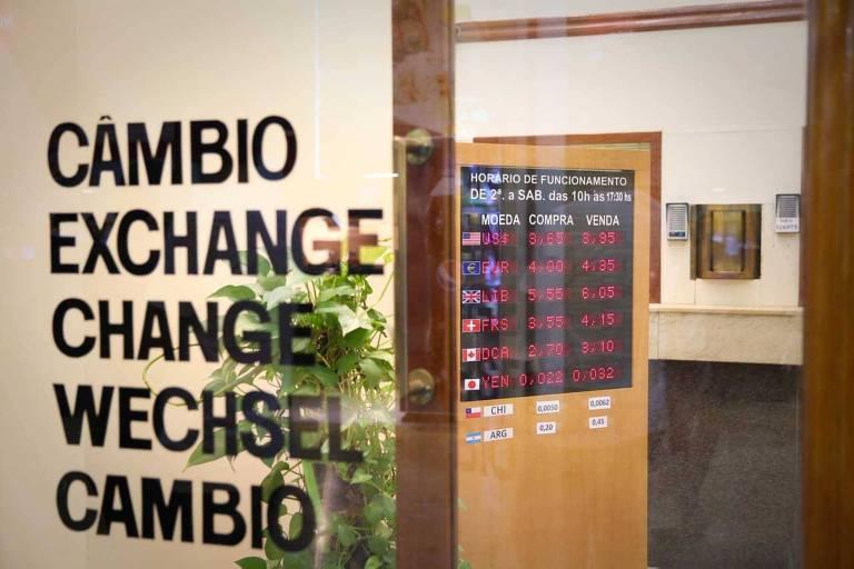 """Parede de vidro com a palavra """"câmbio"""" em várias línguas e interior de escritório ao fundo"""