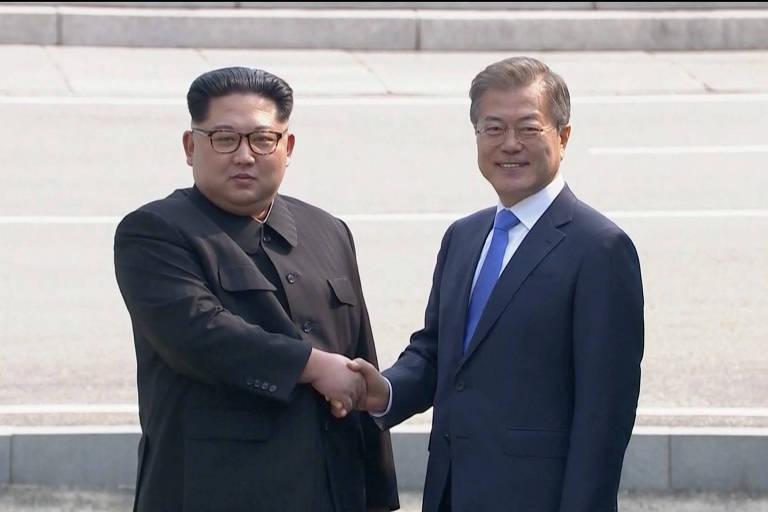 Kim Jong-un aparece de blazer preto, enquanto Moon Jae-in, que sorri, usa terno azul marinho, gravata azul e camisa branca; ao fundo, uma das escadarias de acesso a Panmunjom