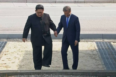 In this image made from video provided by Korea Broadcasting System (KBS), North Korean leader Kim Jong Un, left and South Korean President Moon Jae-in, right, cross the military demarcation line to the South side at the border village of Panmunjom in the Demilitarized Zone Friday, April 27, 2018. Kim made history Friday by crossing over the world's most heavily armed border to greet his rival, Moon, for talks on North Korea's nuclear weapons.(Korea Broadcasting System via AP) ORG XMIT: TOK809