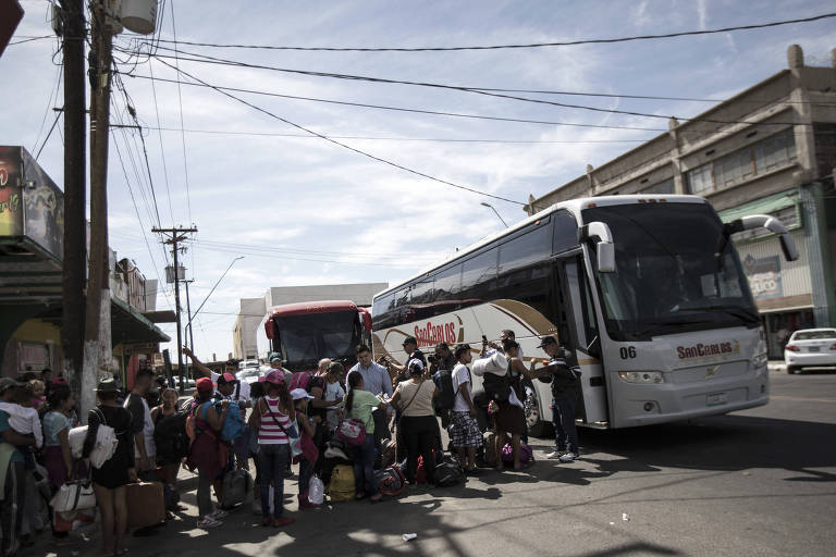Em rua, grupo de pessoas com malas faz fila ao lado da porta de um ônibus rodoviário branco, que está de porta aberta; atrás, outro ônibus espera