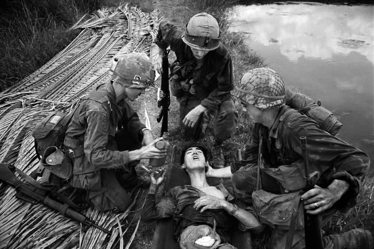 soldados ao redor de vietcong ferido