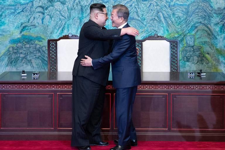 Em pé, o ditador Kim Jong-un (à esq.), com as mãos no ombro do presidente Moon Jae-in, que o enlaça pela cintura, se abraçam e se encaram diante de uma mesa com duas cadeiras usada na cúpula das Coreias