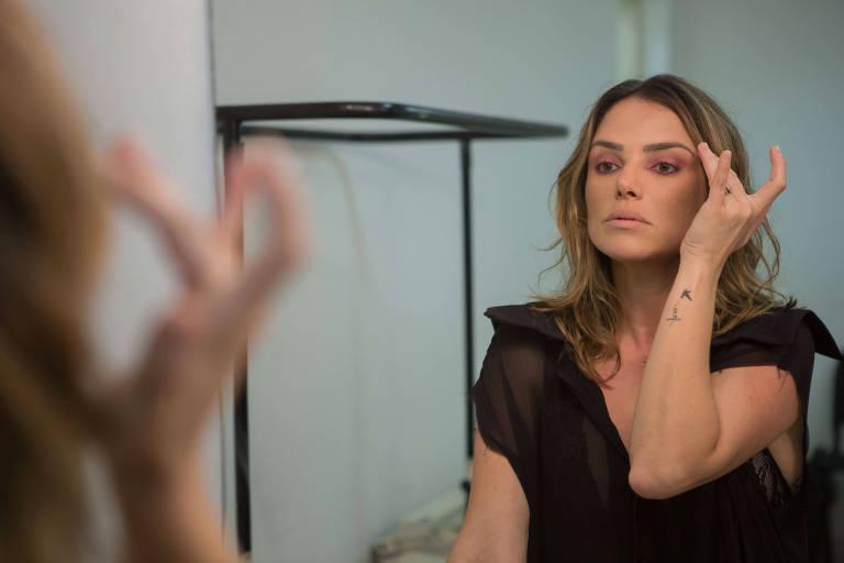 A atriz Natallia Rodrigues passa maquiagem em frente a um espelho