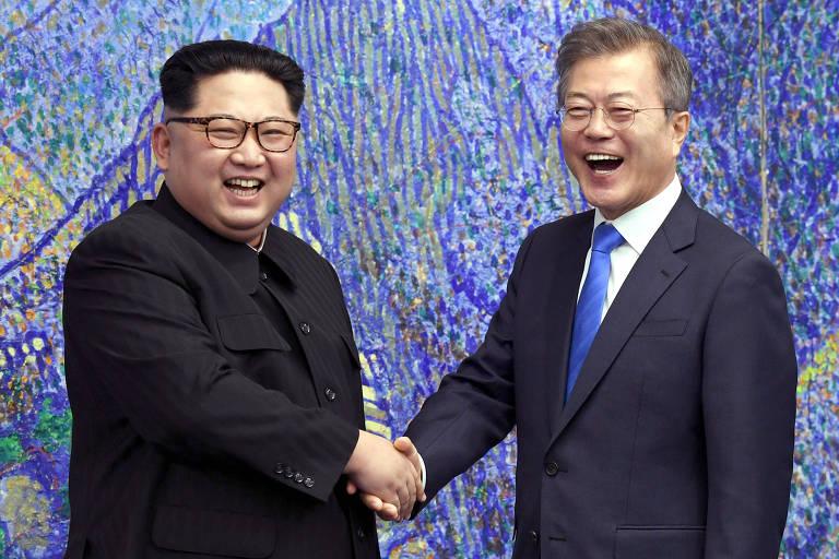 Kim Jong-un aparece à esquerda de blazer preto e óculos escuros e Moon Jae-in usa terno preto, camisa branca e gravata azul royal; os dois aparecem na imagem da cintura para cima e um fundo com uma pintura emulando uma montanha em tons azulados
