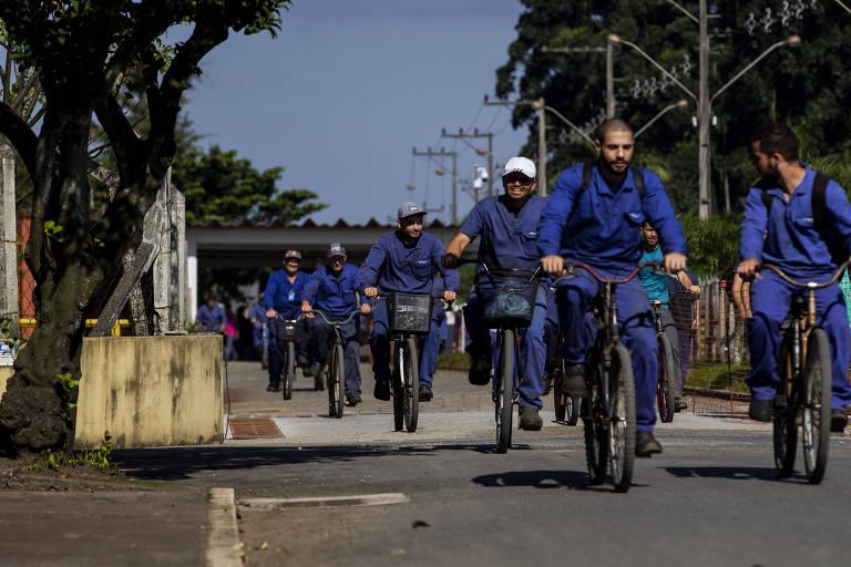 Funcionários da Fundição Tupy, em Joinville (SC), em bicicletas e vestindo os uniformes azuis da empresa