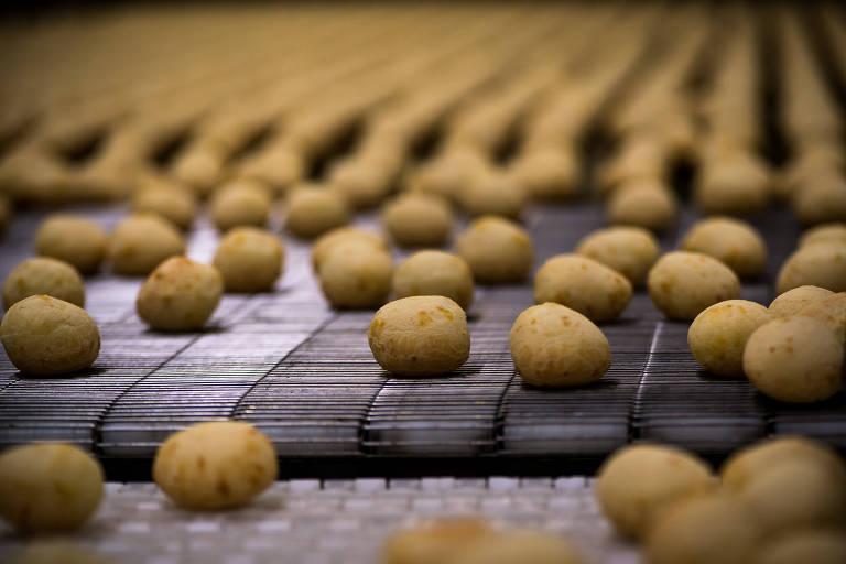 Linha de produção de pão de queijo, com os quitutes já assados passando por esteiras