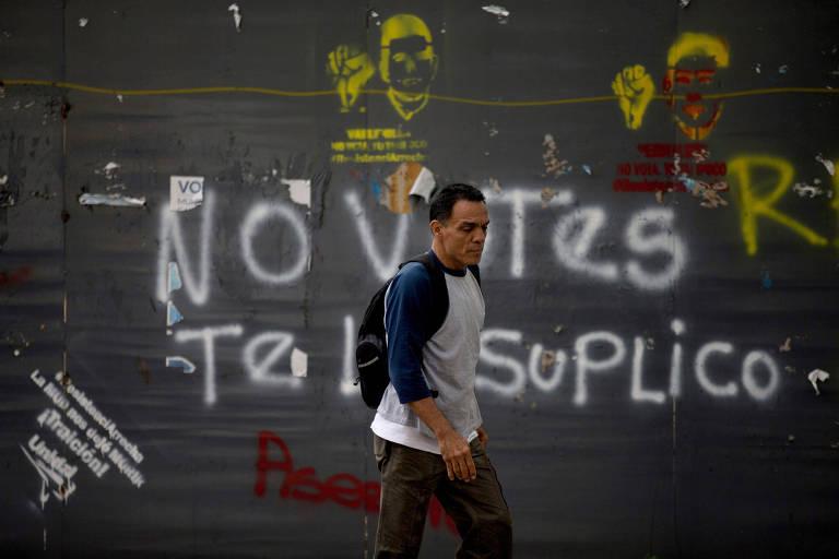"""Homem caminha em frente a muro em Caracas, na Venezuela, onde se lê uma pichação com a expressão """"Não vote, te suplico"""""""