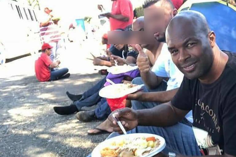 Jefferson Lima de Menezes comendo ao lado outras pessoas no acampamento