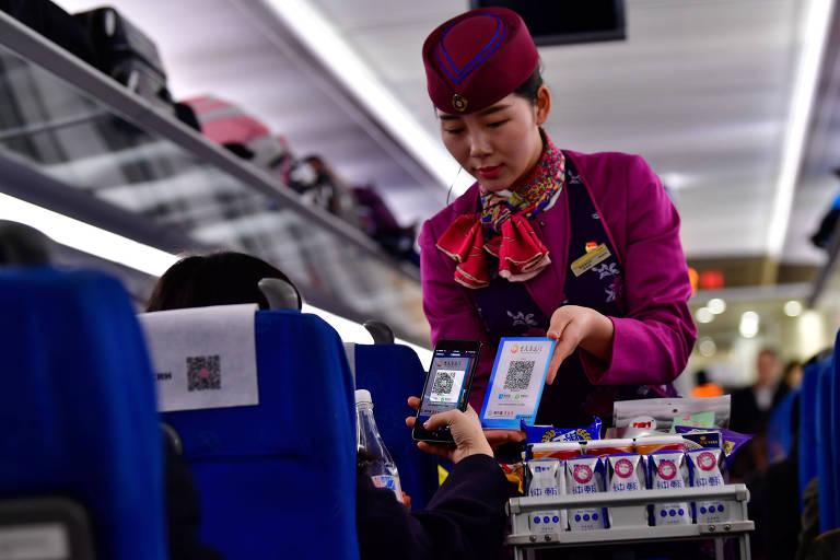 Passageiro faz a leitura de um QR Code para pagar a água que acabou de comprar, na China