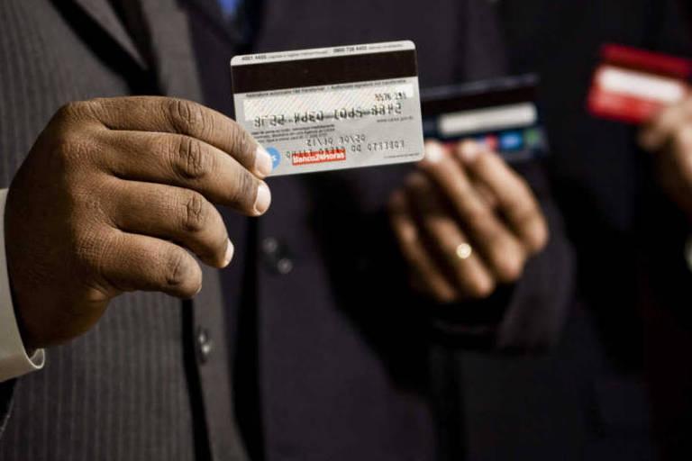 Funcionarios da empresa Arcon mostram seus cartoes de credito, no escritorio da empresa no bairro do Ibirapuera