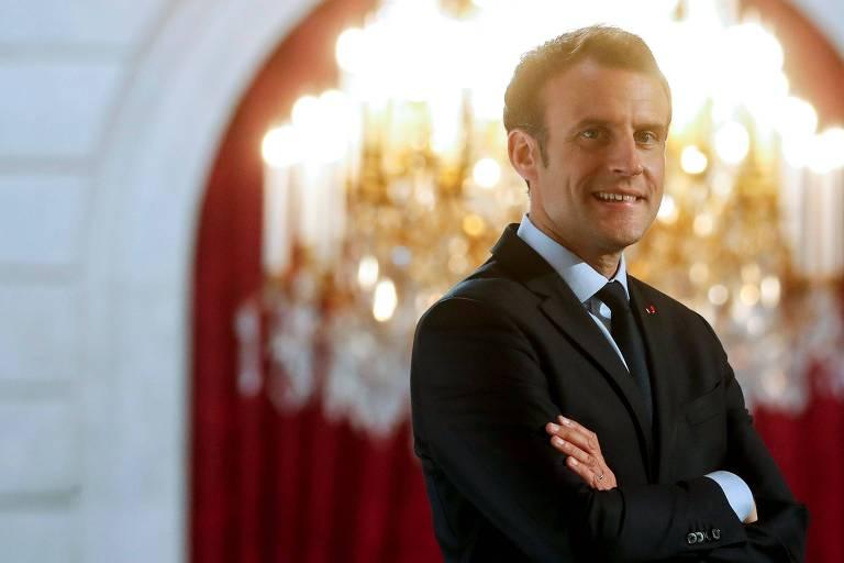 Emmanuel Macron, de terno preto e diante de um candelabro e cortinas vermelhas, encara a câmera de braços cruzados