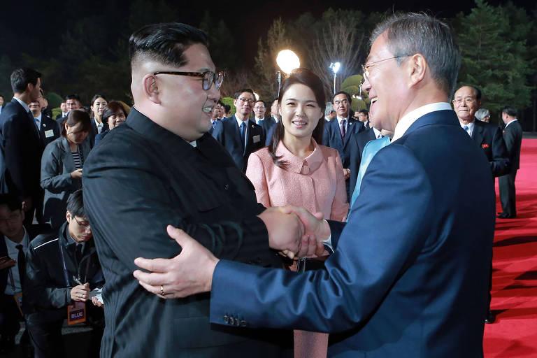 Foto noturna mostra os líderes das duas Coreias segurando nos braços um do outro, sorrindo e se encarando, observados pela primeira-dama da Coreia do Norte atrás, em um tapete vermelho, cercados de jornalistas e assessores