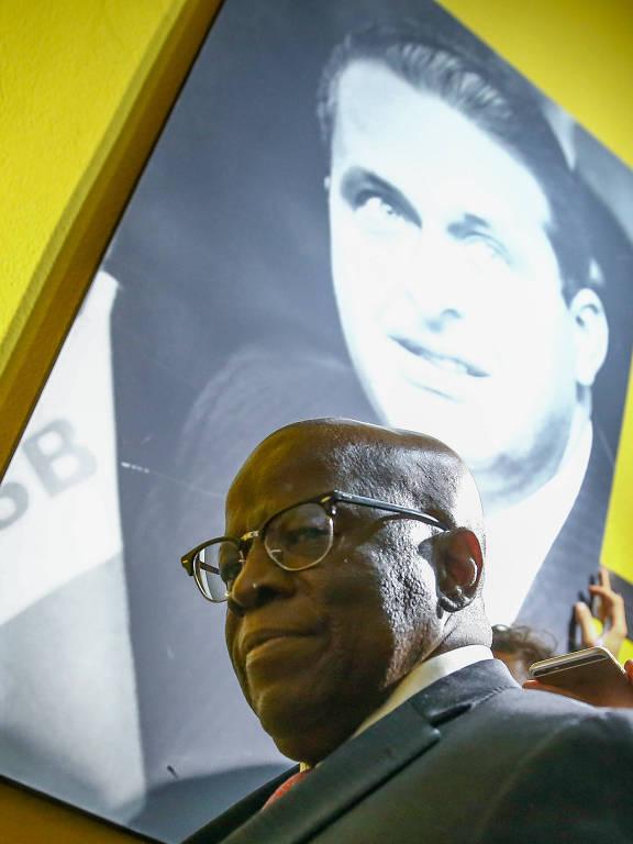 O ex-ministro do STF Joaquim Barbosa em frente a quadro de Eduardo Campos após reunião com políticos do PSB