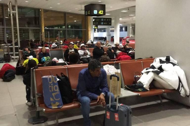 Passageiros no aeroporto de Lisboa enquanto aguardam embarque para o Brasil