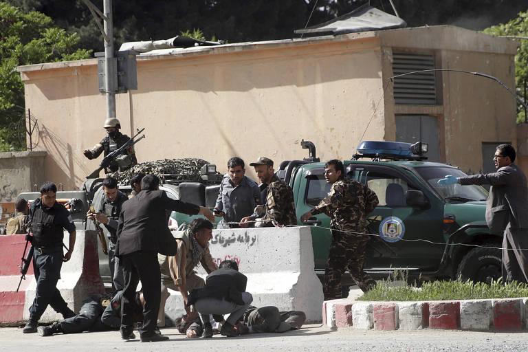 Soldados e agentes de segurança ajudam vítimas de explosões em Cabul nesta segunda-feira (30)