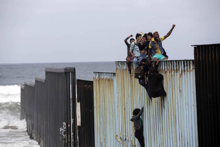 Migrantes da caravana vinda da América Central protestam em cima da cerca na fronteira entre EUA e México