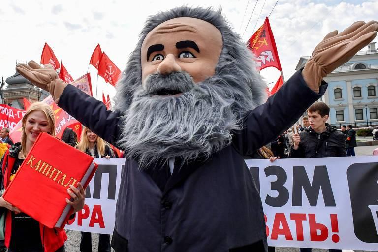 Manifestante vestido de Karl Mark participa de marcha do 1º de Maio em Moscou