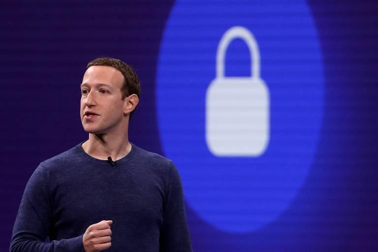 Mark Zuckerberg com braço esquerdo dobrado na altura do peito. Em uma tela ao fundo, há um sinal de cadeado fechado, num fundo azul