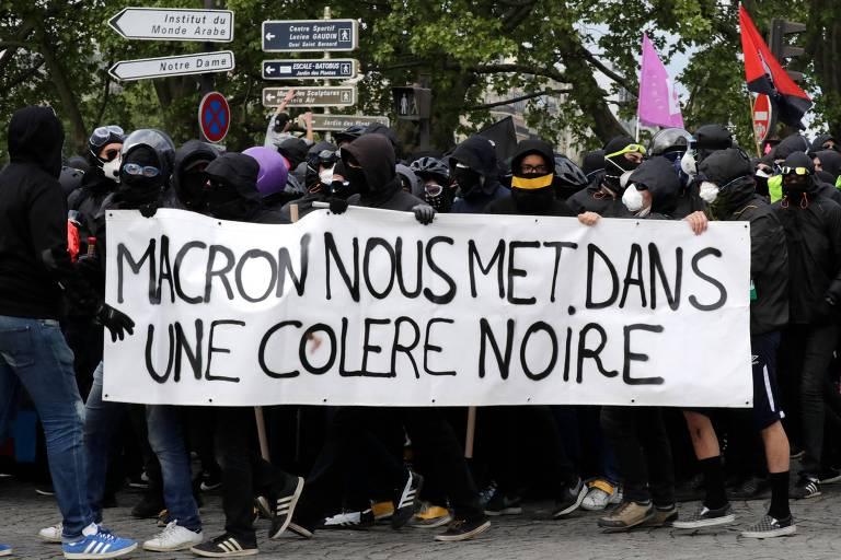 """Manifestantes vestidos de preto seguram faixa que diz """"Macron nos deixa furioso"""" enquanto participam de ato de 1º de maio em Paris"""