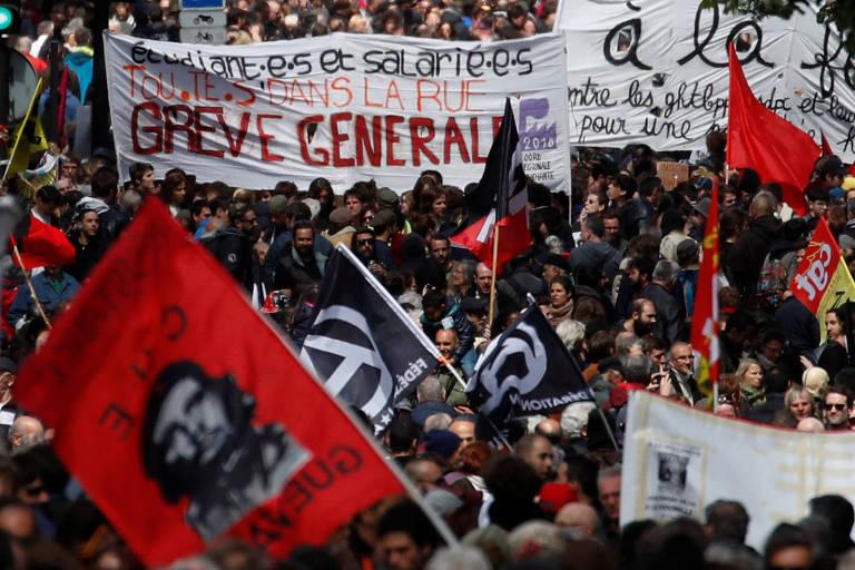 Manifestantes com cartaz convocando greve geral participam de ato de 1º de Maio em Paris