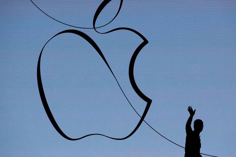 Tim Cook, CEO da Apple, acena enquanto faz uma apresentação e um palco com o símbolo da Apple de fundo