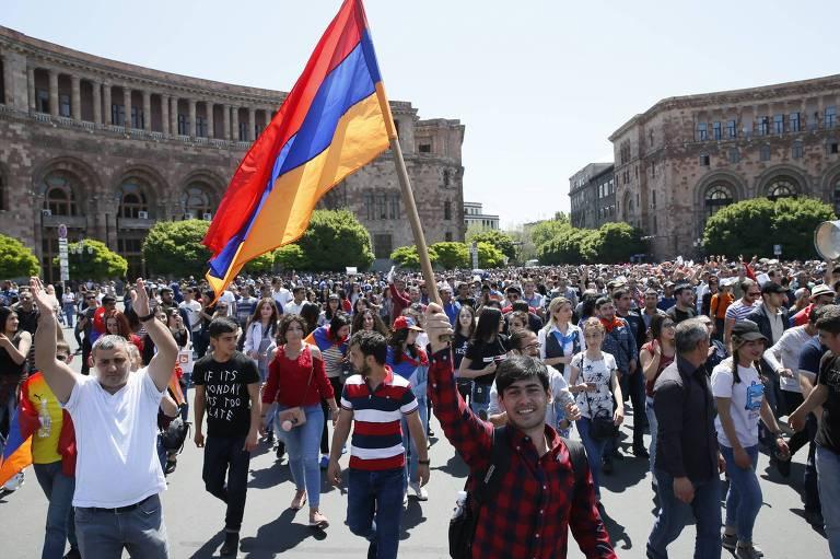 Homem com bandeira em meio a multidão