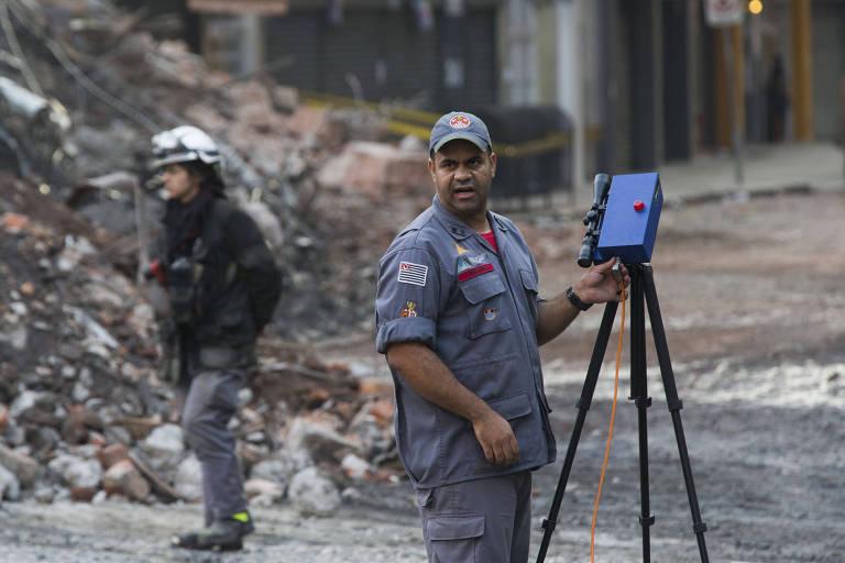 Bombeiro manipula detector a laser que monitora risco desabamento de prédio vizinho ao que caiu no centro de SP
