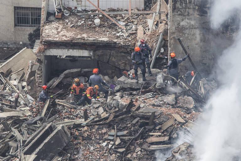 Bombeiros caminham sobre escombros em busca de desaparecidos após desabamento de prédio no centro de São Paulo