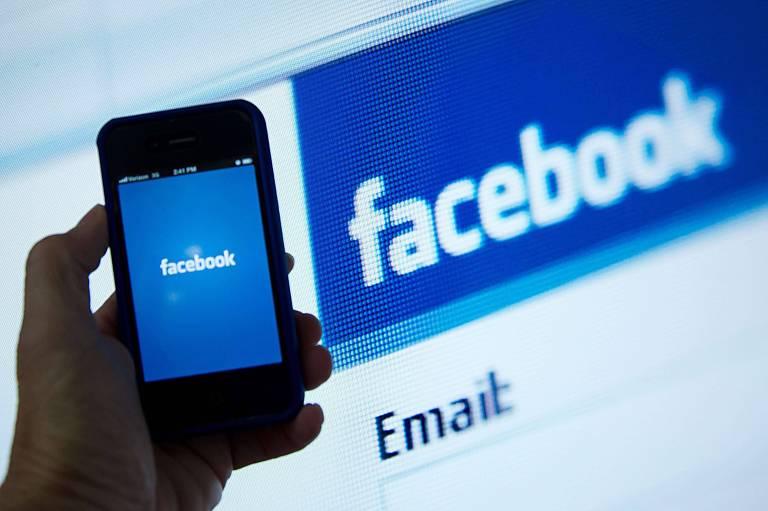 Usuário acessa Facebook pelo celular, com tela da rede social ao fundo