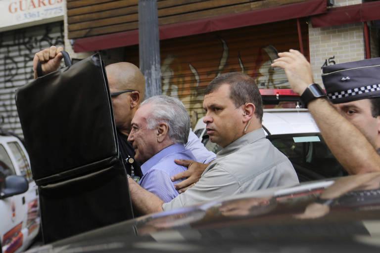 Guarda costas tentam proteger Michel Temer enquanto pessoas gritam e jogam objetos contra ele; o presidente foi à área onde o prédio desabou, no centro de São Paulo