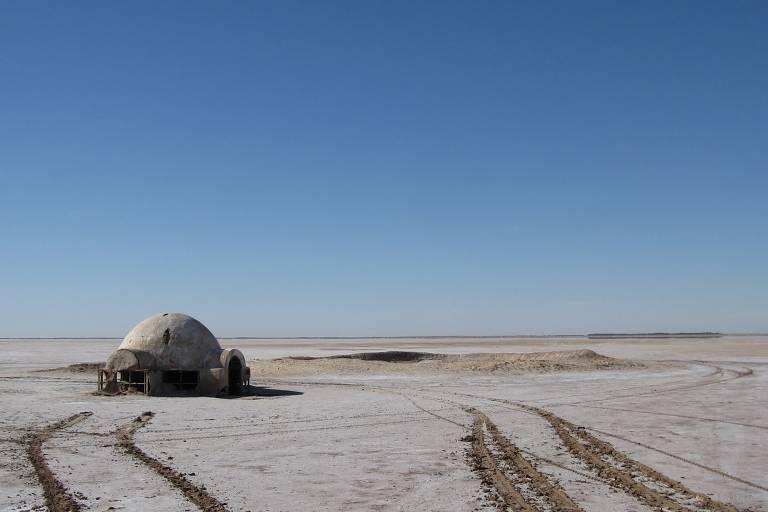Iglu de pedra branca que fica em meio a um deserto de sal plano na Tunísia. Ao lado dele, há uma grande cratera