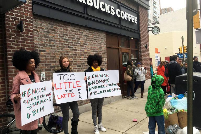 Três mulheres negras seguram cartazes de protestos em frente ao Starbucks da Filadélfia, onde dois fregueses negros foram detidos por estarem sentados a uma mesa da loja sem terem feito pedidos
