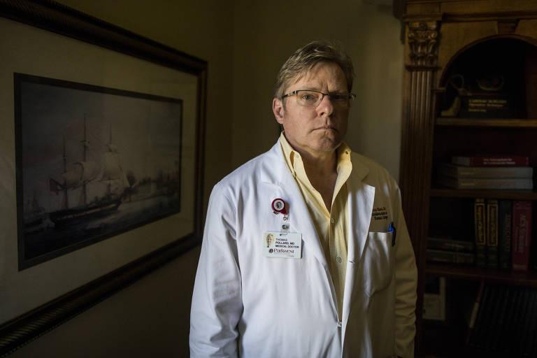O médico Thomas Pollard posa, com jaleco branco e camisa amarela, para foto
