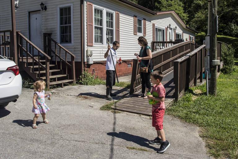 Na entrada de uma casa, os filhos de Jerika Whitefield brincam. Enquanto isso, ela conversa com seu marido Chris Bunch
