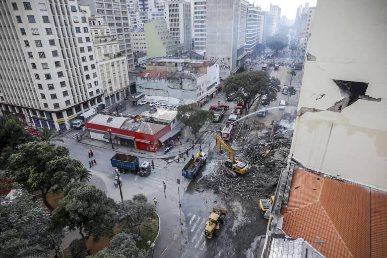 Bombeiros trabalham com retroescavadeira para tirar os escombros do local de desabamento