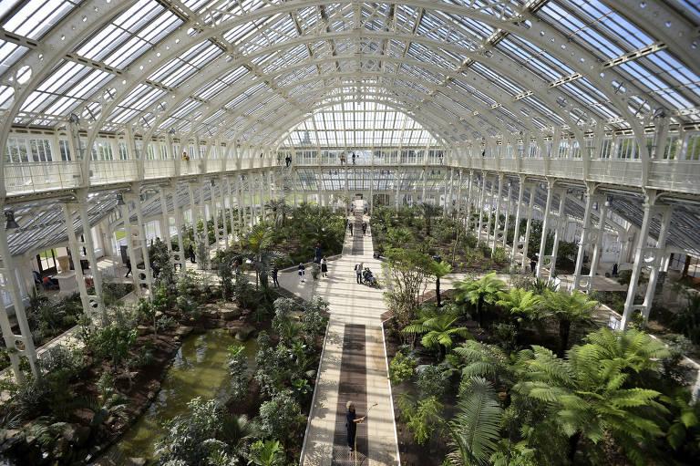 Interior da estufa de vidro do jardim botânico de Londres. A estufa tem estrutura em ferro fundido branco e em barras de diferentes espessuras. Entre elas, há painéis de vidro. A foto foi tirada de uma plataforma superior de observação dentro da estufa, da qual é possível ver todo o jardim no térreo. O espaço é bastante amplo e iluminado