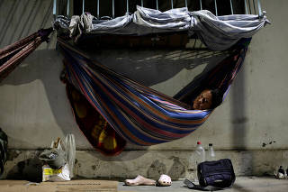 Venezuelan refugee Gabriela Martinez, who worked as a telecommunications engineer, relaxes in a hammock near a bus station in Manaus, Brazil